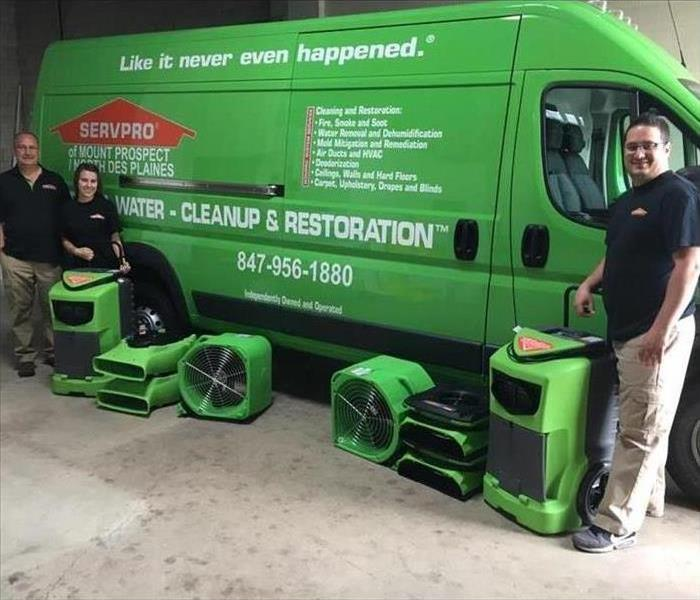 Three team member in front of a green mini van and air movers
