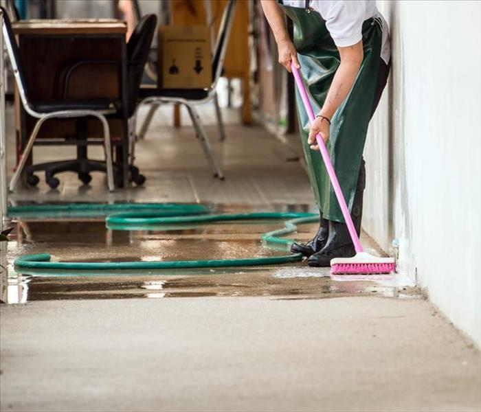 Worker scrubbing the floor with a brush, wet floor surface