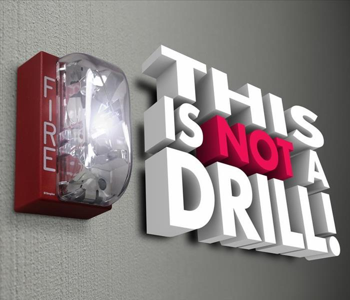 "Fire alarm with sign ""this is not a drill"""